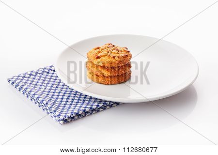 Stack of three homemade peanut butter cookies on white ceramic plate on blue napkin