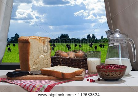 Country products - milk in the glass eggs in a basket, fresh white bread, a jug of milk and a bowl o