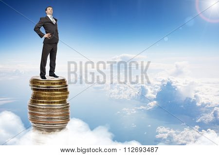 Businessman on coins pile in sky