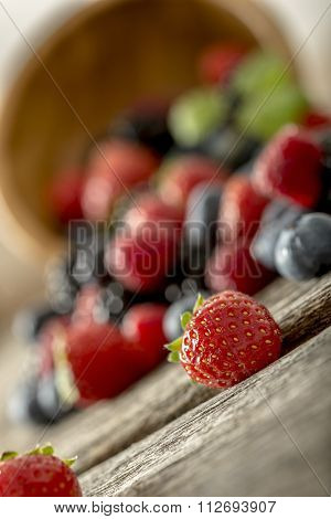 Closeup Of Juicy Ripe Mixed Berry Fruits Scattering Out Of Wooden Bowl
