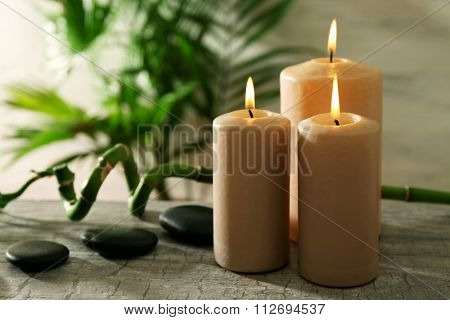Spa composition of candles, stones and bamboo on light background