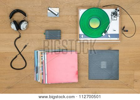 Directly above shot of turntable with records and headphones on table