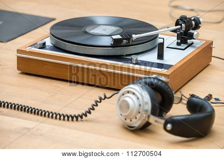 Closeup of turntable and headphones on wooden table