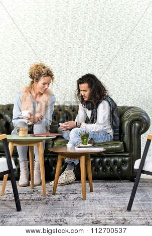 Young man showing a woman a few photos on his smart phone, sitting on a luxurious couch in a retro styled lounge