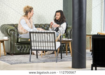 Man and woman during a personal conversation, sitting on a leather couch in a lounge of a stylish retro coffee corner