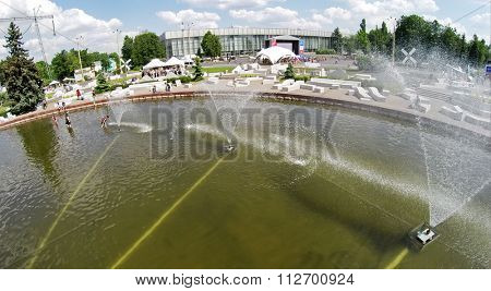 RUSSIA, MOSCOW - MAY 24, 2014: People walk in fountain on Industrial Square at territory of All Russia Exhibition center in spring sunny day. Aerial view