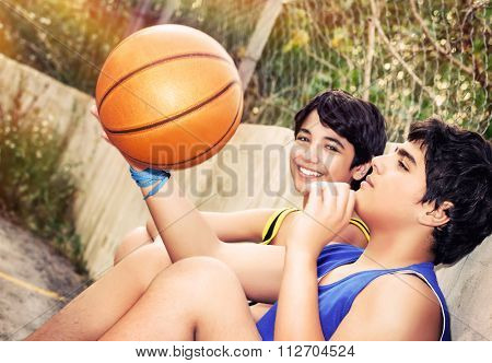 Cute basketball players sitting and resting in timeout, two teenage boys enjoying outdoor game, happy healthy active lifestyle
