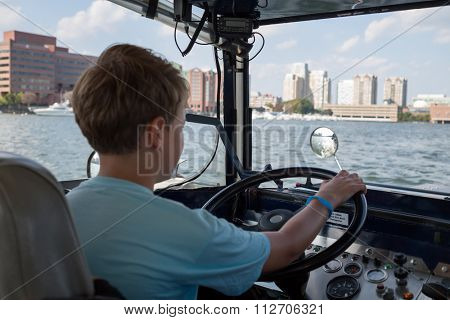 Young boy is driving amphibian car on the water (focus on the front panel).