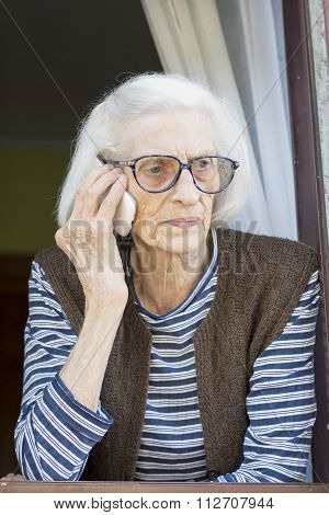 Old Grandma Talking On The Phone Standing On Her Window