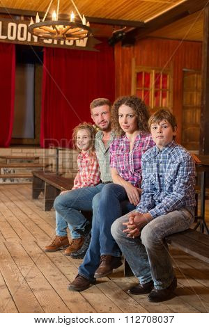 family of four sitting on a bench in saloon