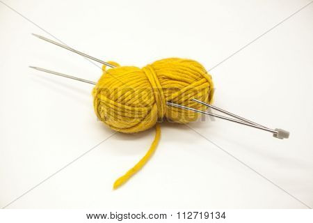 Yellow ball of yarn for knitting with spokes on a white background