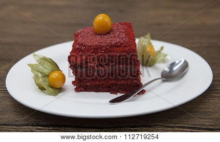 Red Velvet, fresh delicious diet cake with berry Physalis at Dukan Diet on a porcelain plate with a spoon on a wooden background.