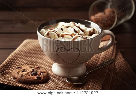 Mug of hot chocolate with marshmallows, on wooden background