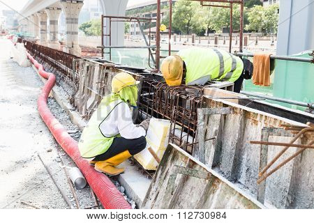 Two Workers Fitting Wooden Mould Onto Rebar At Construction Site