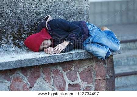 Young Homeless Boy Sleeping On The Street