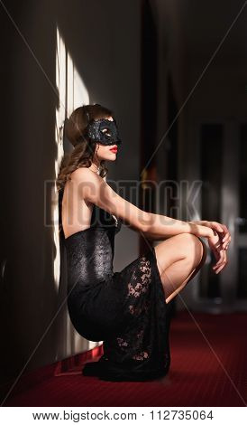 Portrait of attractive sensual young woman with mask, indoors. Sexy brunette lady posing provocative