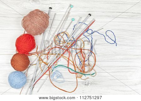 Tangled Threads With Yarn Balls And Needles On Wooden Board.