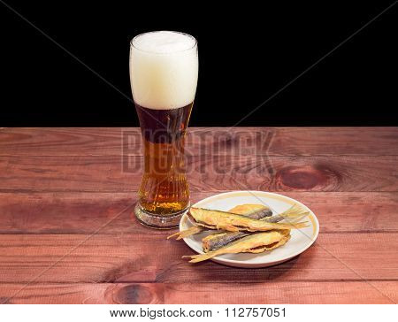 Glass Of Beer And Fish Snack On Wooden Surface