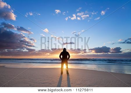 Man On The Beach In Front Of Rising Sun
