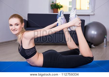Slim Flexible Woman Doing Exercise On Yoga Mat