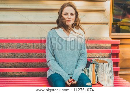 Young Woman With Face With Freckles Is Siting On A Bench. Outdoor Picture In Full Man's Length.