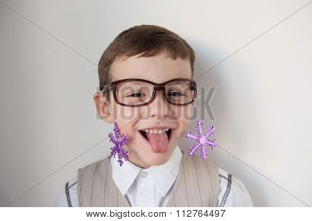 boy with glasses attached to them snowflakes showing tongue
