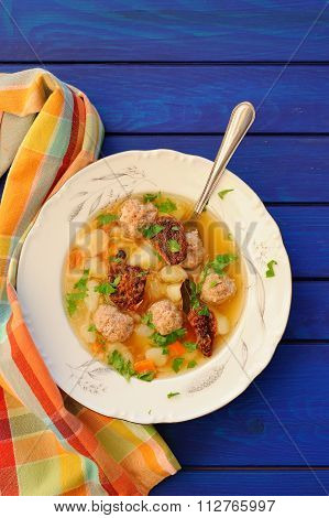 Meatball Soup With Sundried Tomatoes On Deep Blue Wooden Table