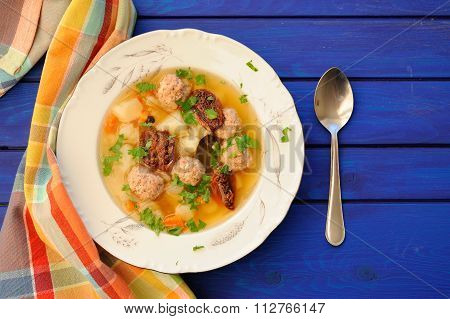Meatball Soup With Sundried Tomatoes And Spoon On Deep Blue Wooden Table