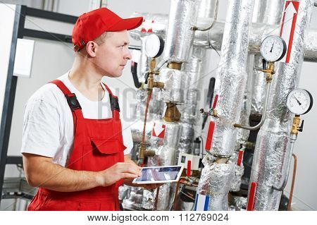 Technician maintenance repairman engineer inspecting heating system in boiler room