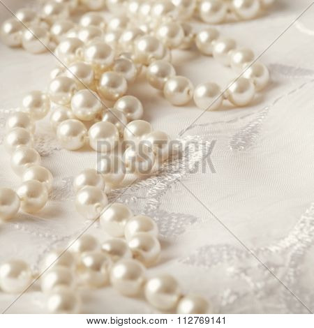 wedding pearl necklace on white floral background