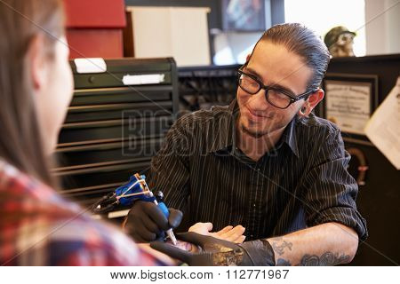 Tattoo Artist Working On Design For Female Client