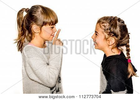 Little Girl Telling Her Sister To Shut Up With Her Finger On The Mouth. A Gesture Of Silence . Close
