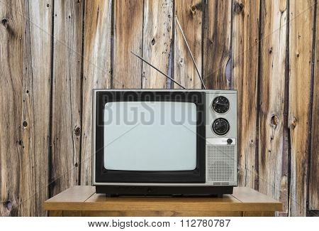 Vintage television on table with rustic wood wall.