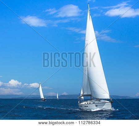 Sailing ships yachts with white sails in the open sea. Sailing yacht race.