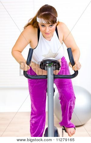 Smiling pregnant woman working out on static bike at home