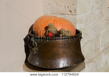 Pumpkin With Bottles Of Potions In A Copper Vat On Wall Background. Horizontal View