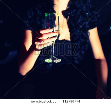 Woman with glas of white vine in her hand in night club