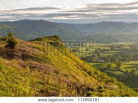 View Over Llangedwyn Valley With Figure On Headland