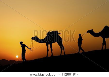 Silhouette of the Camel Trader across the sand dune during sunset at Sunset Point Pushkar.