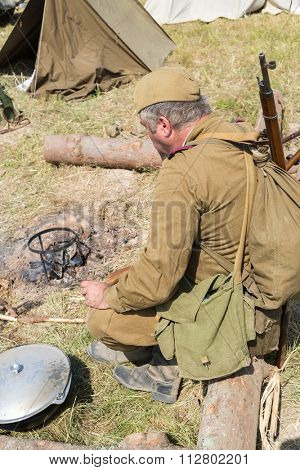 soldier sitting on a log in the fire extinct