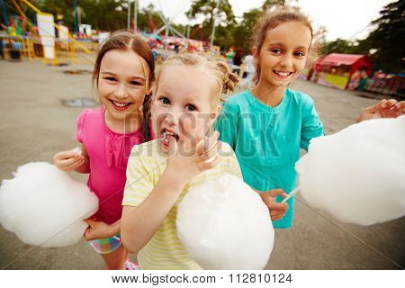Happy girls eating cotton candy in the park