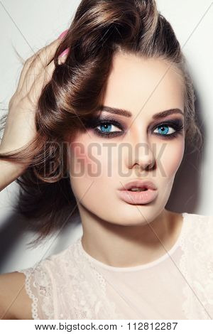 Portrait of young beautiful blue-eyed woman with stylish make-up touching her hair
