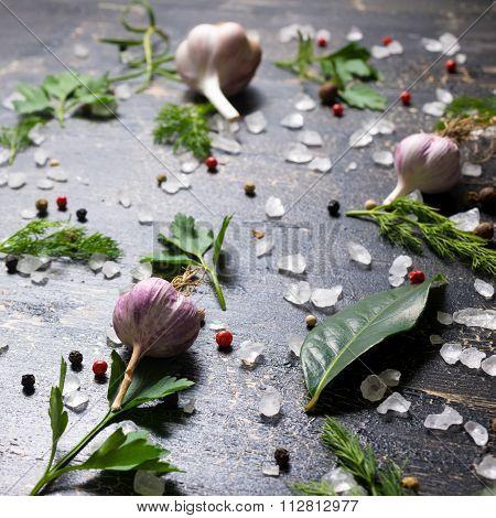 Garlic, Red, Black Peppers, Sea Salt, Greenery On Cracks Black Background, Close Up