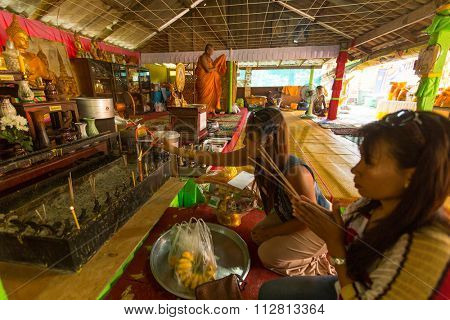 KOH CHANG - THAILAND - DEC 29, 2015: Unidentified local women during visit in the Wat Khlong Prao monastery. Koh Chang one of the largest Islands of Thailand, located of 310 km from Bangkok.