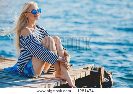 Beautiful Girl in sea style sitting on wooden bridge.