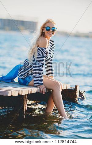 Beautiful Girl in sea style sitting on wooden bridge.