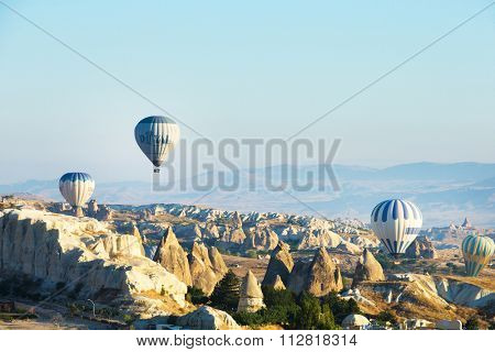 CAPPADOCIA TURKEY - APRIL 16 ,2015 : tourists fly over the amazing landscape of Cappadocia , on the hot air balloons.