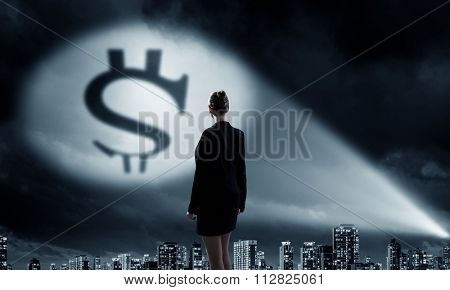 Businesswoman standing with back in darkness and dollar sign in spothlight