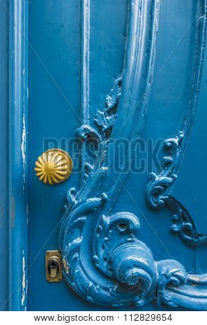 Old wooden door with ornaments and golden doorknob