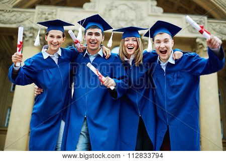 Group of ecstatic graduates with diplomas